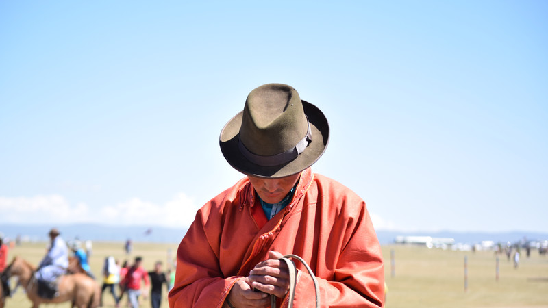 Intrepid Travel-mongolia_local-texting-on-horse